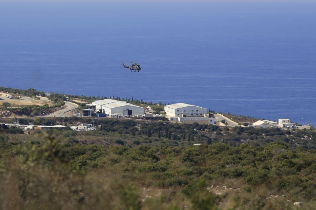 FILE - In this Oct. 14, 2020 file photo, a helicopter flies over a base of the U.N. peacekeeping force, in the southern town of Naqoura, Lebanon. On W...