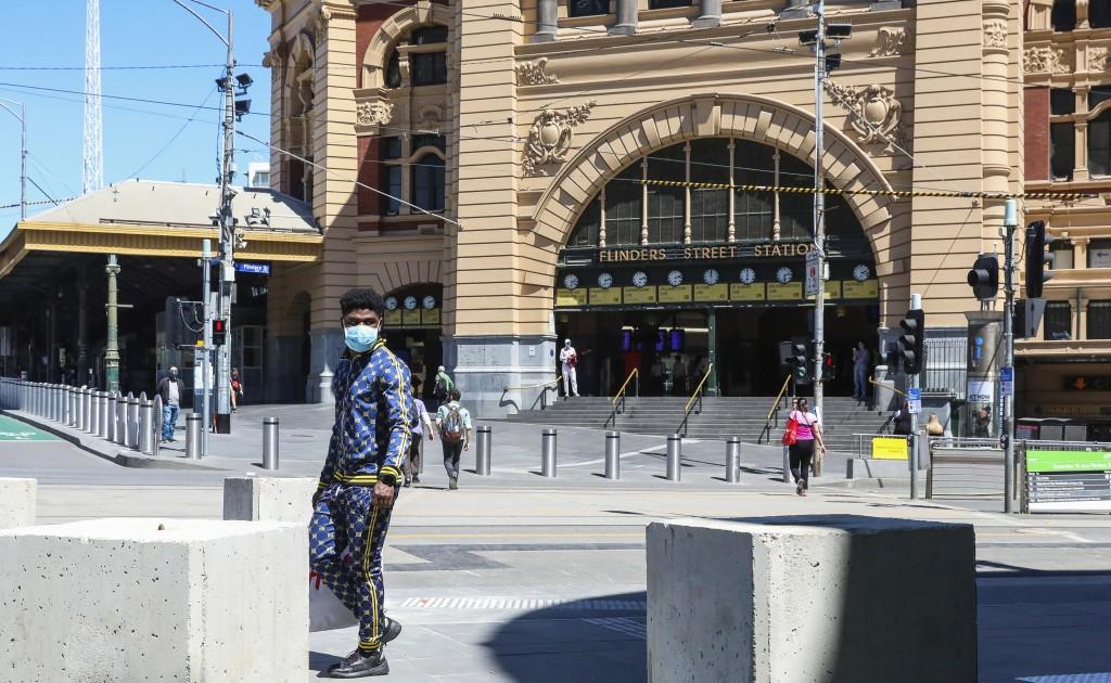 A man wearing a mask walks past Flinders Street Station in Melbourne, Australia, Wednesday, Oct. 28, 2020. In Melbourne, Australia's former coronaviru...