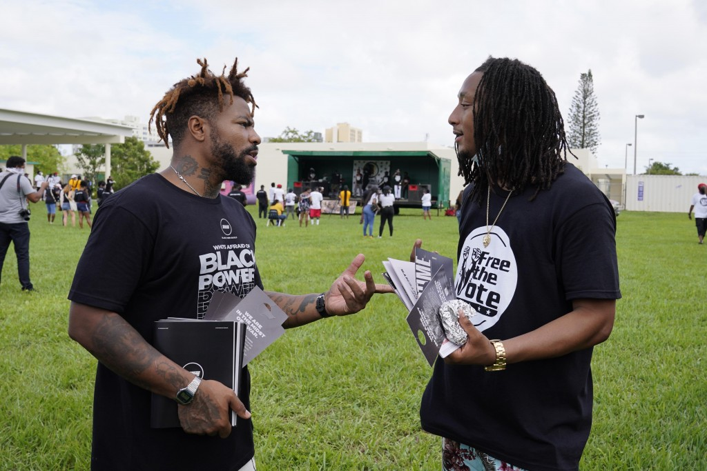 "Phillip Agnew, left, a leader of Black Men Build, speaks with Robert Holness at a ""Free the Vote"" march to the polls, Saturday, Oct. 24, 2020, in Miam..."