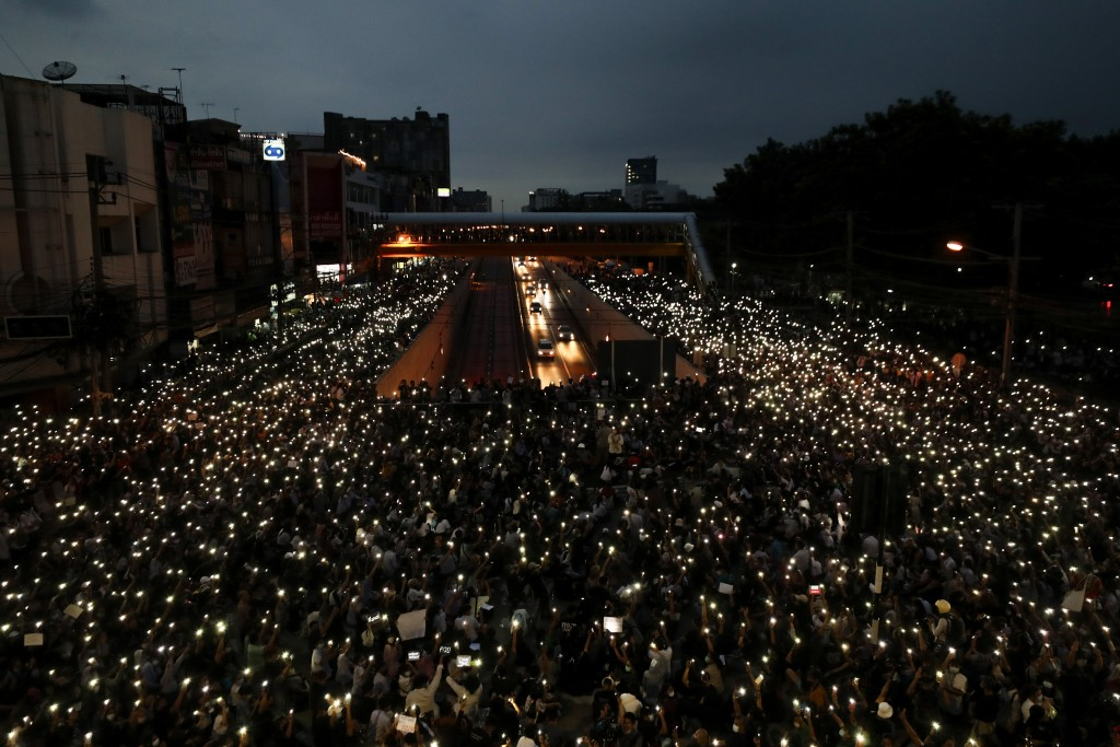 FILE - In this Oct. 19, 2020, file photo, pro-democracy activists wave mobile phones with lights during a demonstration at Kaset intersection, suburbs...