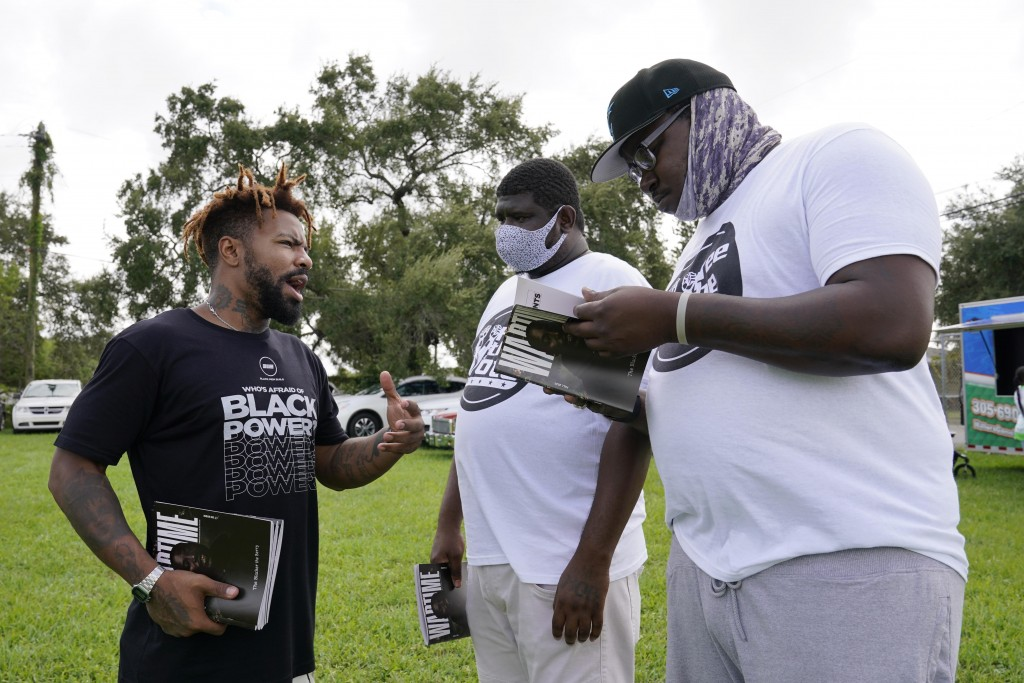 "Phillip Agnew, left, a leader of Black Men Build, speaks to Derrick Williams, right, and Davion Frazier at a ""Free the Vote"" rally to the polls, Satur..."