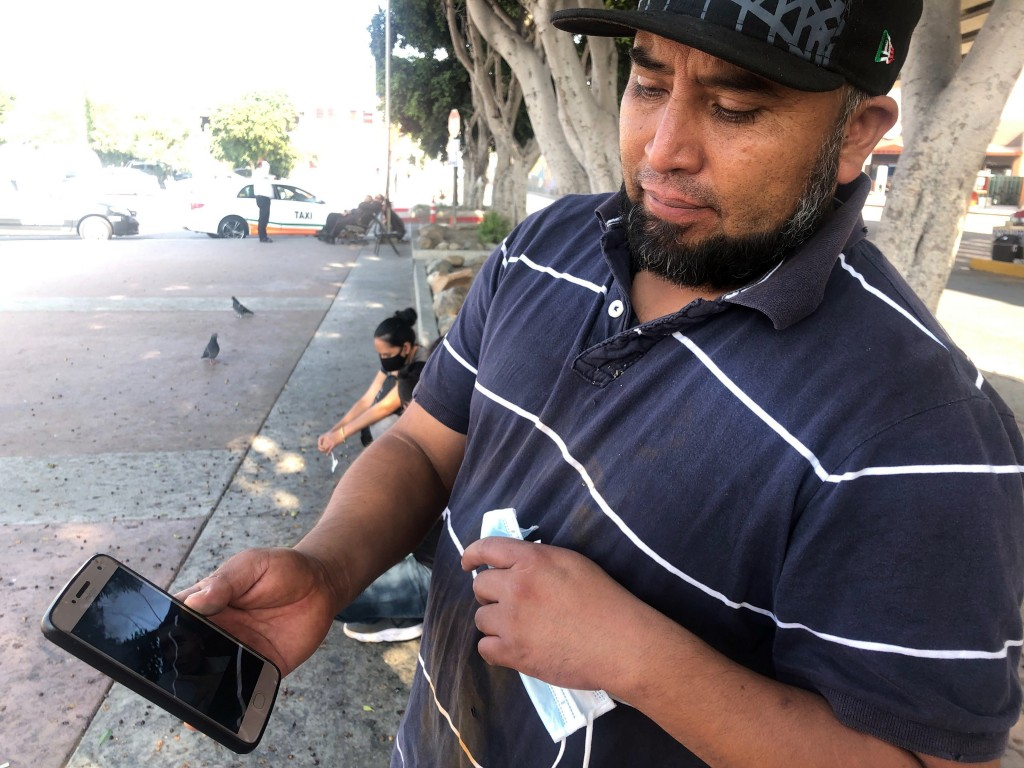 José Edgar Zuleta shows a photo in Tijuana, Mexico, of his 21-year-old on Oct. 9, 2020. Zuleta, whose business selling religious jewelry in the Mexica...