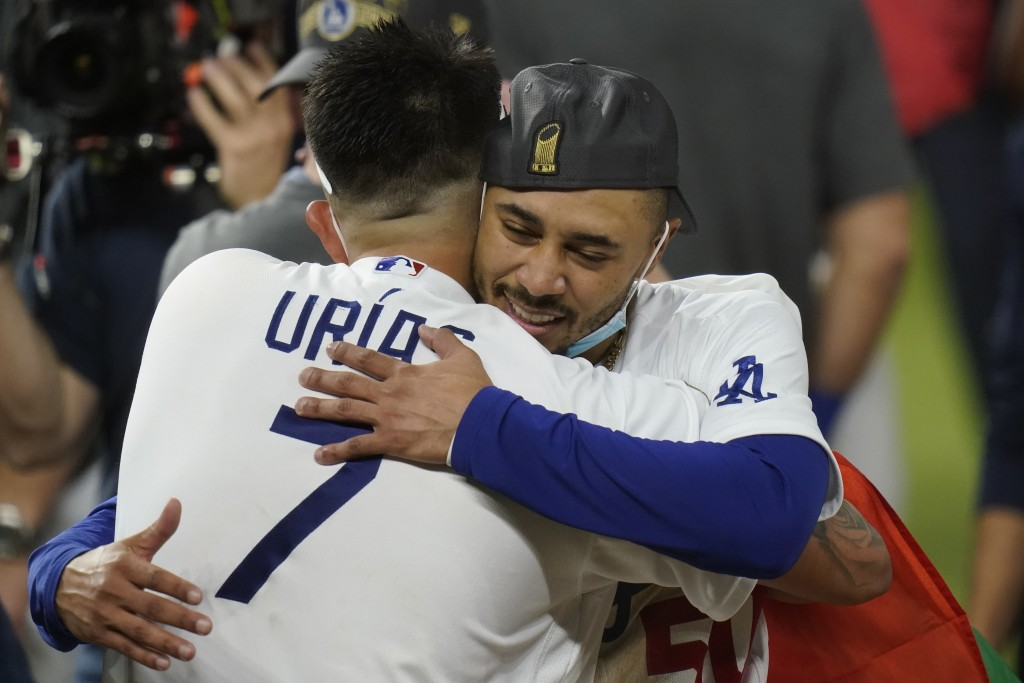 Los Angeles Dodgers pitcher Julio Urias and Mookie Betts celebrate after defeating the Tampa Bay Rays 3-1 to win the baseball World Series in Game 6 T...