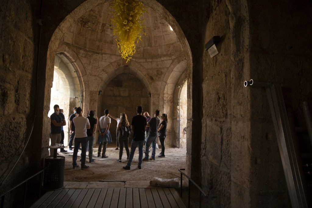 A group gathers under a work by American sculptor Dale Chihuly at the Tower of David Museum in the Old City of Jerusalem, Wednesday, Oct. 28, 2020. Th...
