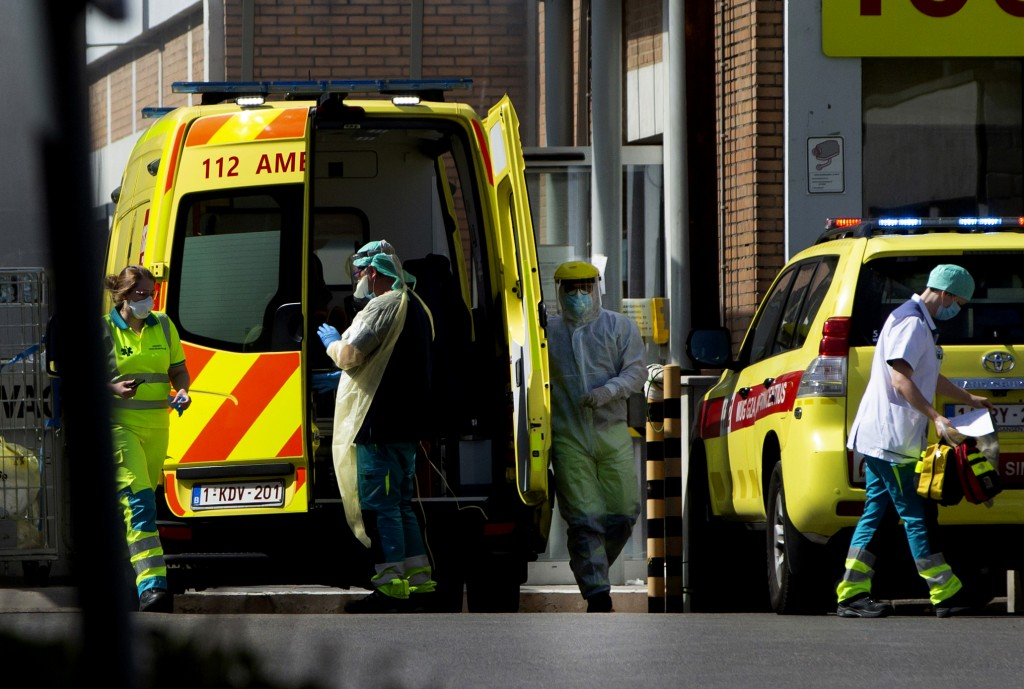 FILE - In this Monday, April 13, 2020 file photo, medical personnel in protective gear prepare to receive a patient at a hospital in Antwerp, Belgium....