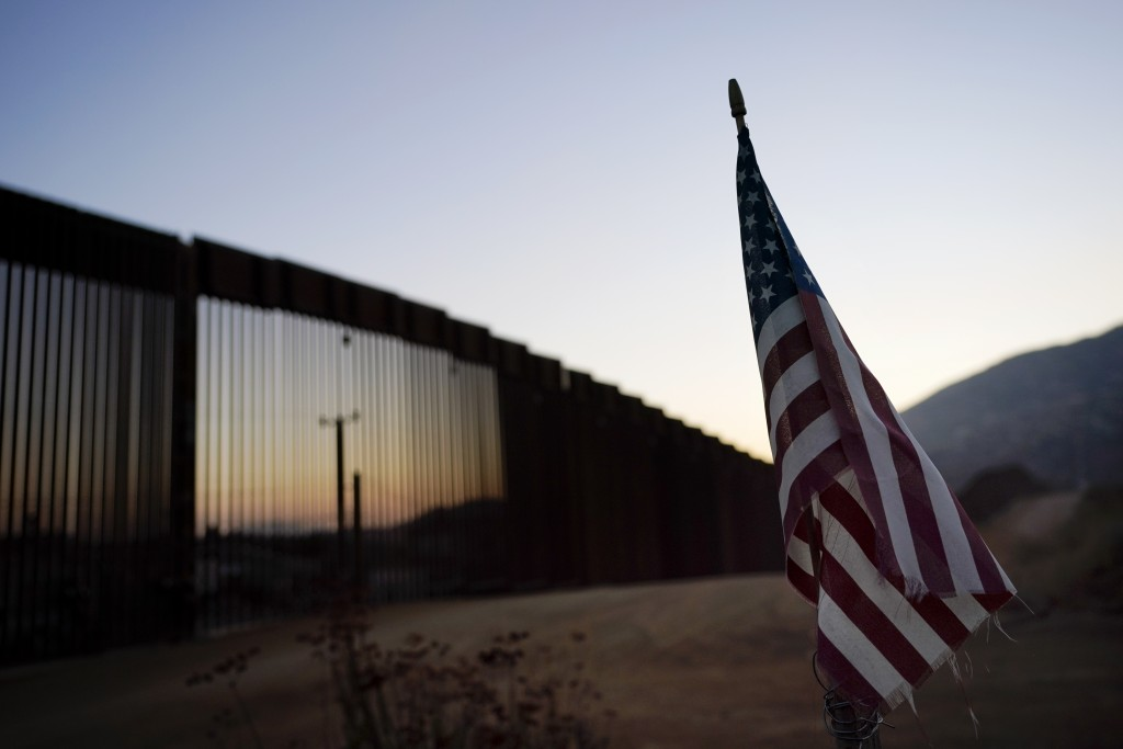 A flag sits just north of a new section of the border structure, behind, Thursday, Sept. 24, 2020, near Tecate, Calif. President Donald Trump's reshap...
