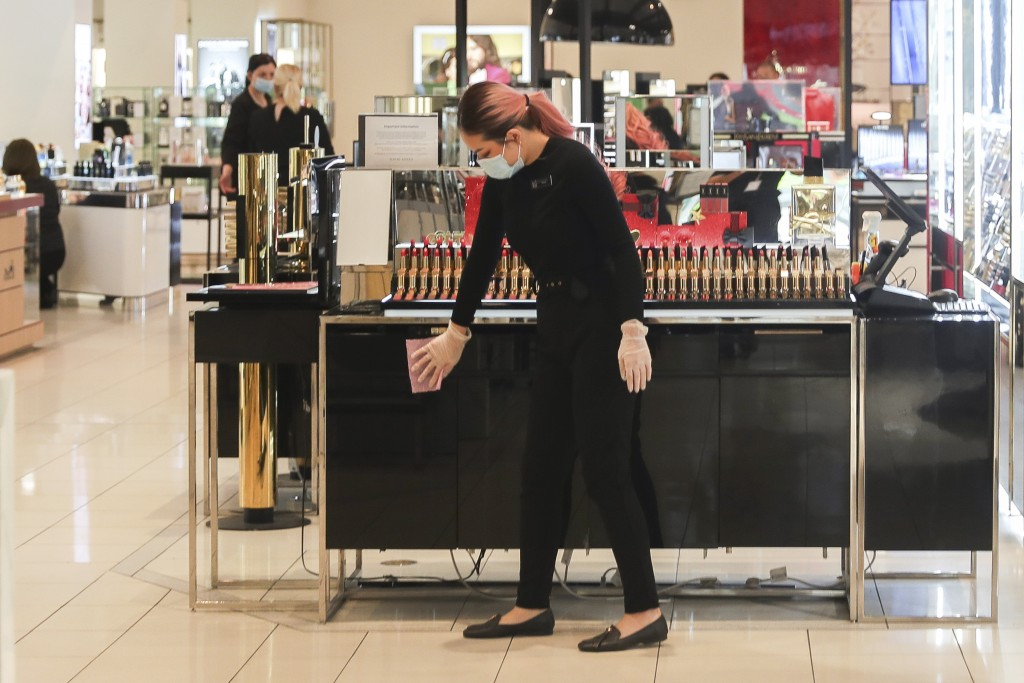 A worker inside a retail department store wipes down a cosmetics display shelf in Melbourne, Australia, Wednesday, Oct. 28, 2020. Australia's second l...