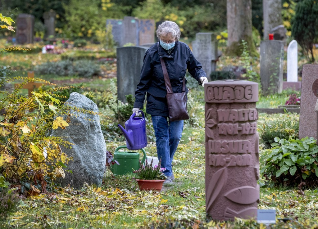 An elderly woman wearing a face mask takes care of a grave at the main cemetery in Frankfurt, Germany, Wednesday, Oct. 28, 2020. (AP Photo/Michael Pro...