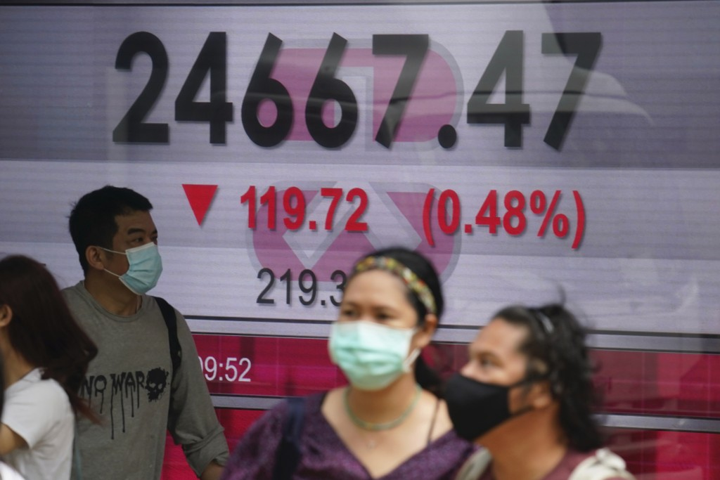 People wearing face masks walk past a bank's electronic board showing the Hong Kong share index in Hong Kong, Wednesday, Oct. 28, 2020. Asian shares h...