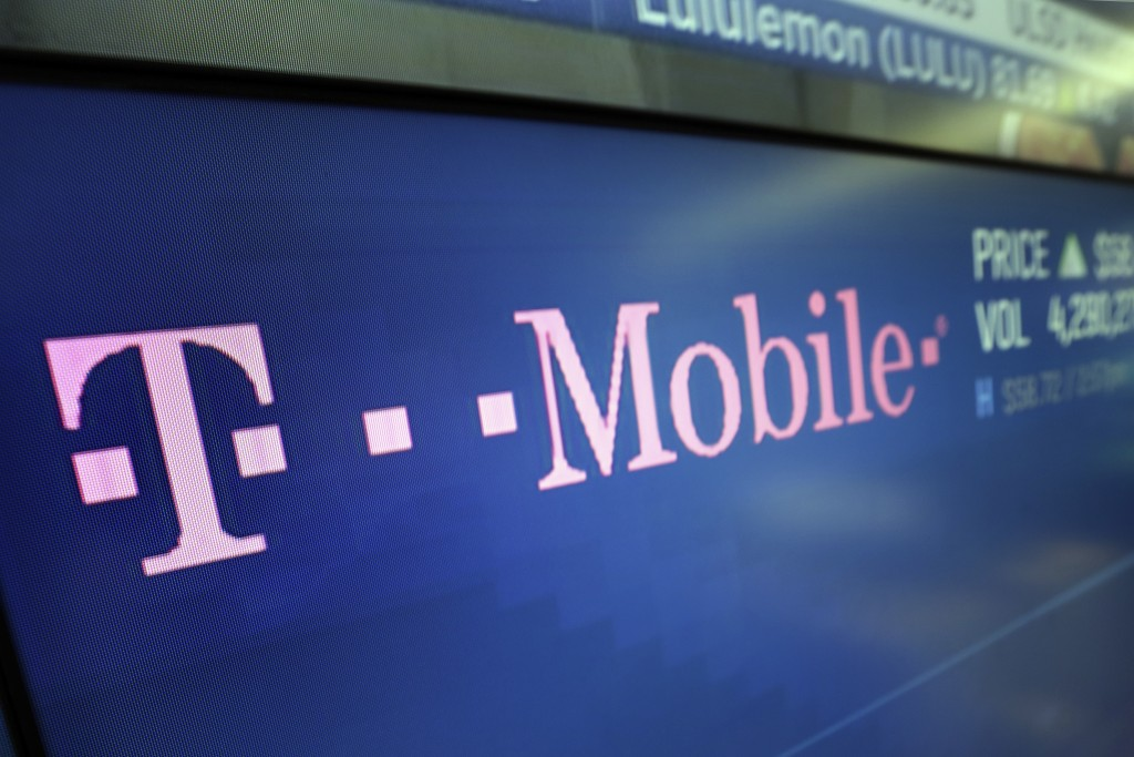 FILE - In this Feb. 14, 2018, file photo, the T-Mobile logo ppears on a screen at the Nasdaq MarketSite in New York. Yet another service provider is j...
