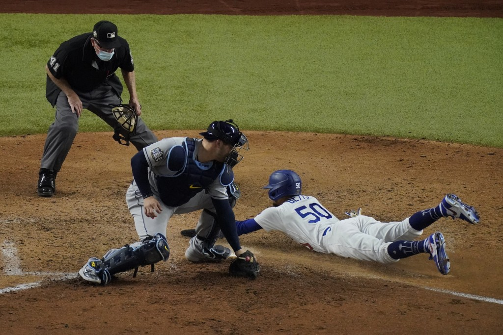 Los Angeles Dodgers' Mookie Betts scores past Tampa Bay Rays catcher Mike Zunino during the sixth inning in Game 6 of the baseball World Series Tuesda...