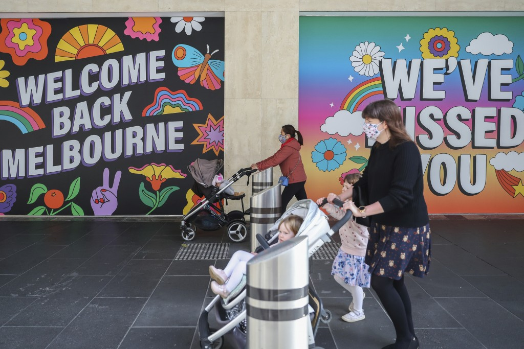 Women wearing face masks push strollers past signage in Melbourne, Australia, Wednesday, Oct. 28, 2020. Australia's second largest city of Melbourne w...