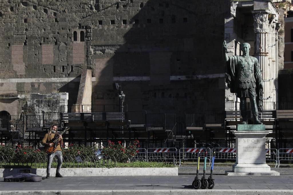 A street musician performs with his electric guitar beside the statue of Roman Emperor Julius Cesar on a almost empty Via Dei FOri Imperiali avenue in...