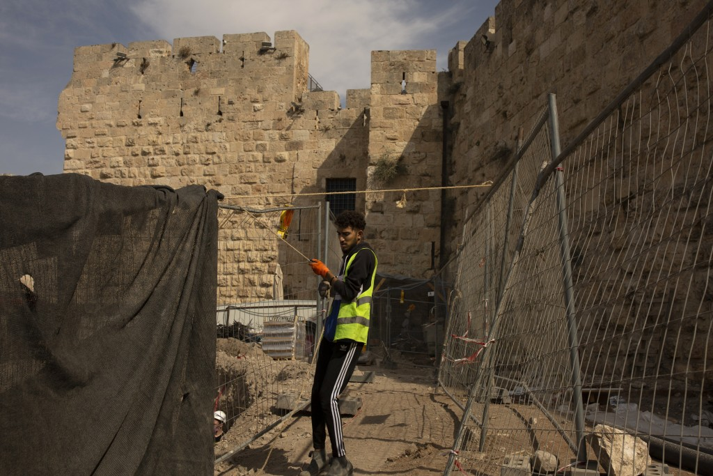 A worker places netting at a construction site inside the Tower of David Museum in the Old City of Jerusalem, Wednesday, Oct. 28, 2020. Jerusalem's an...