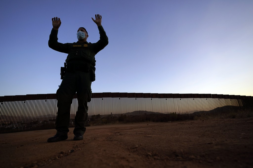 Border Patrol agent Justin Castrejon gestures as he describes the difficulties of climbing the new section of the border structure, behind, Thursday, ...