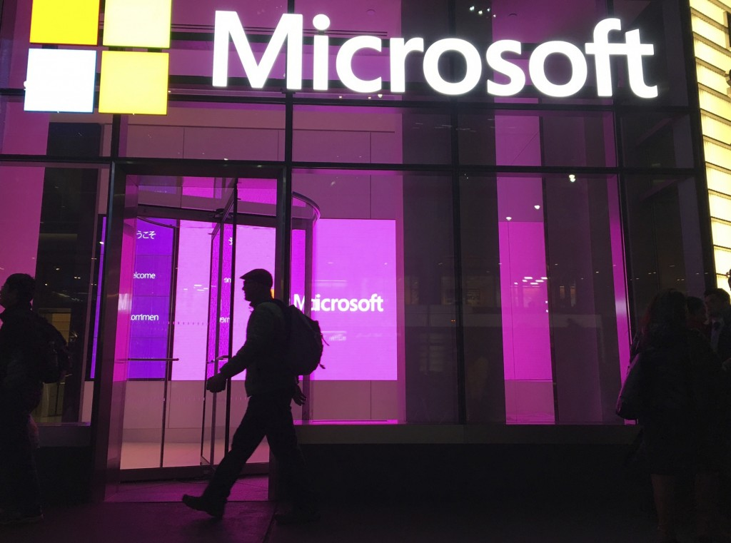 FILE - In this Nov. 10, 2016, photo, people walk near a Microsoft office in New York.  Microsoft says Iranian hackers have posed as conference organiz...
