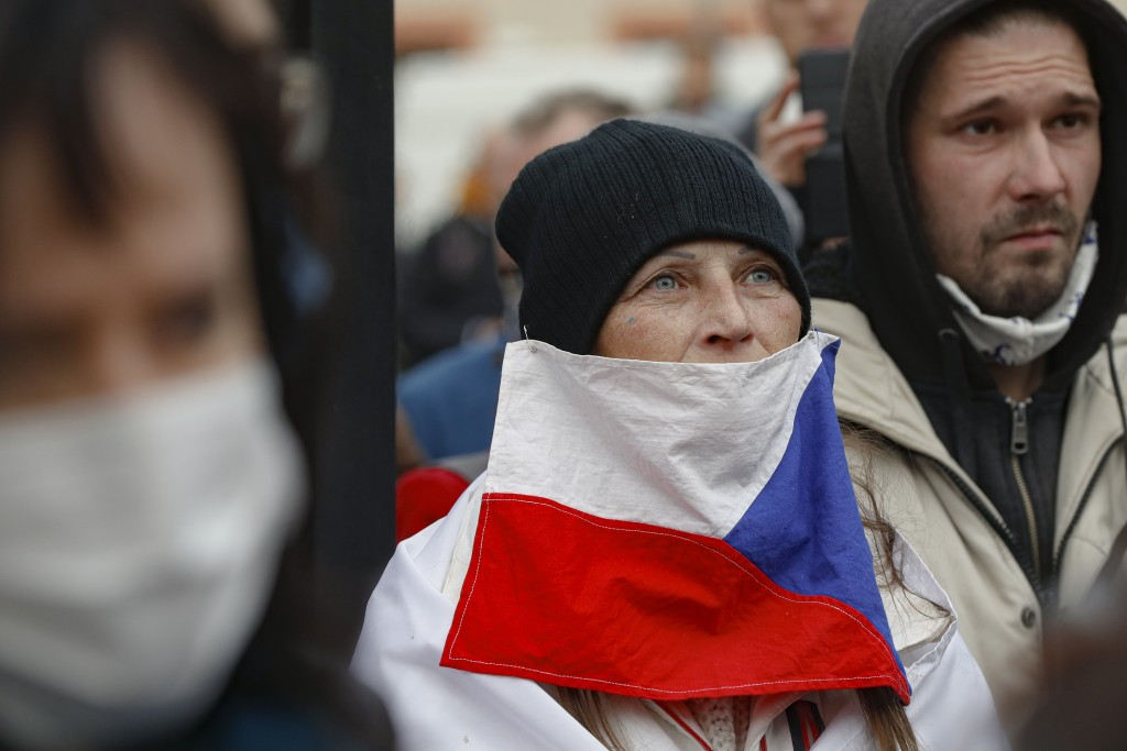 Woman wears a Czech flag asmask as demonstrators gather to protest COVID-19 preventative measures downtown Prague Oct. 28, 2020.