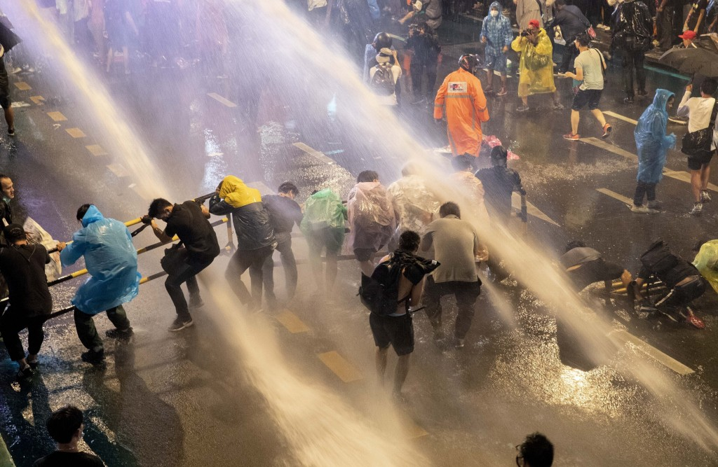 FILE - In this Oct. 16, 2020, file photo, pro-democracy demonstrators face water cannons as police try to disperse them from their protest venue in Ba...