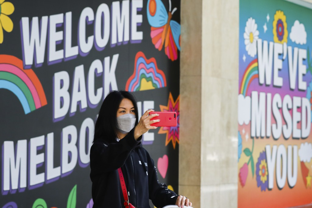 A woman takes a selfie in front of signage in Melbourne, Australia, Wednesday, Oct. 28, 2020. Australia's second largest city of Melbourne which was a...