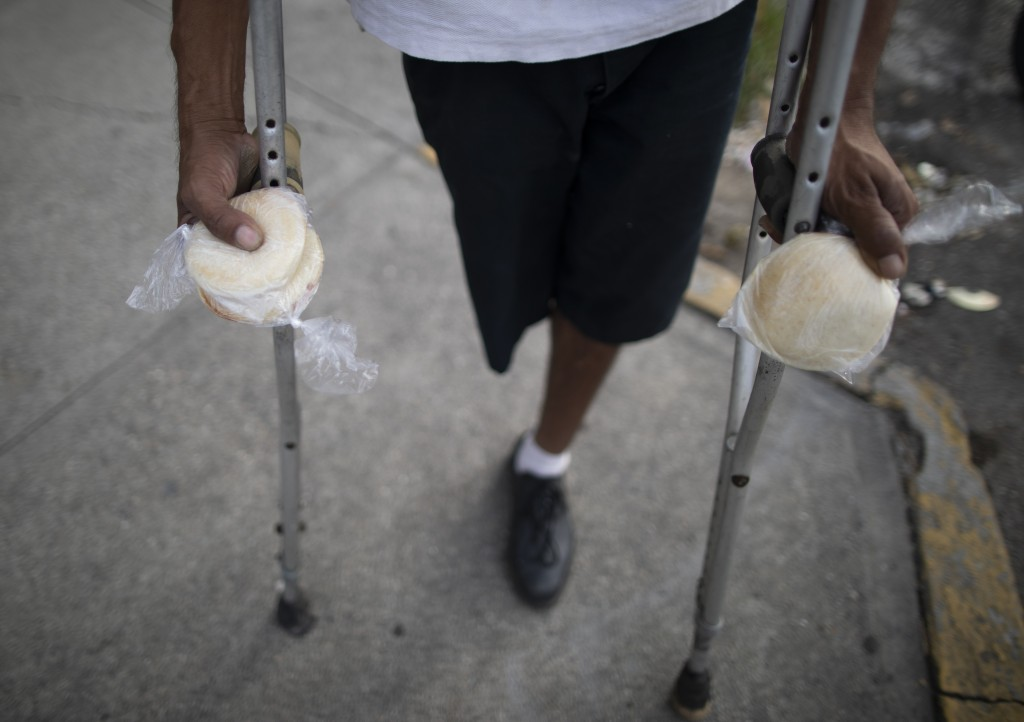 A man on crutches holds packages of homemade arepas given to him by 55-year-old publicist Andres Burgos, who started handing out the corn flour pattie...