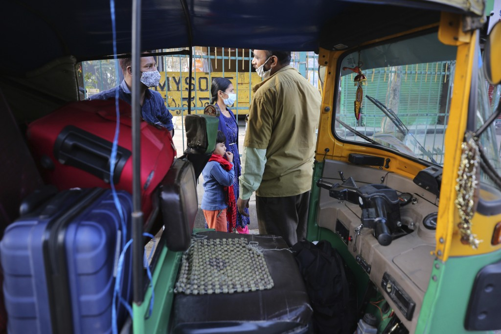 An Indian family wearing face masks as a precaution against the coronavirus bargain for a ride with an autorickshaw driver in Bengaluru, India, Thursd...