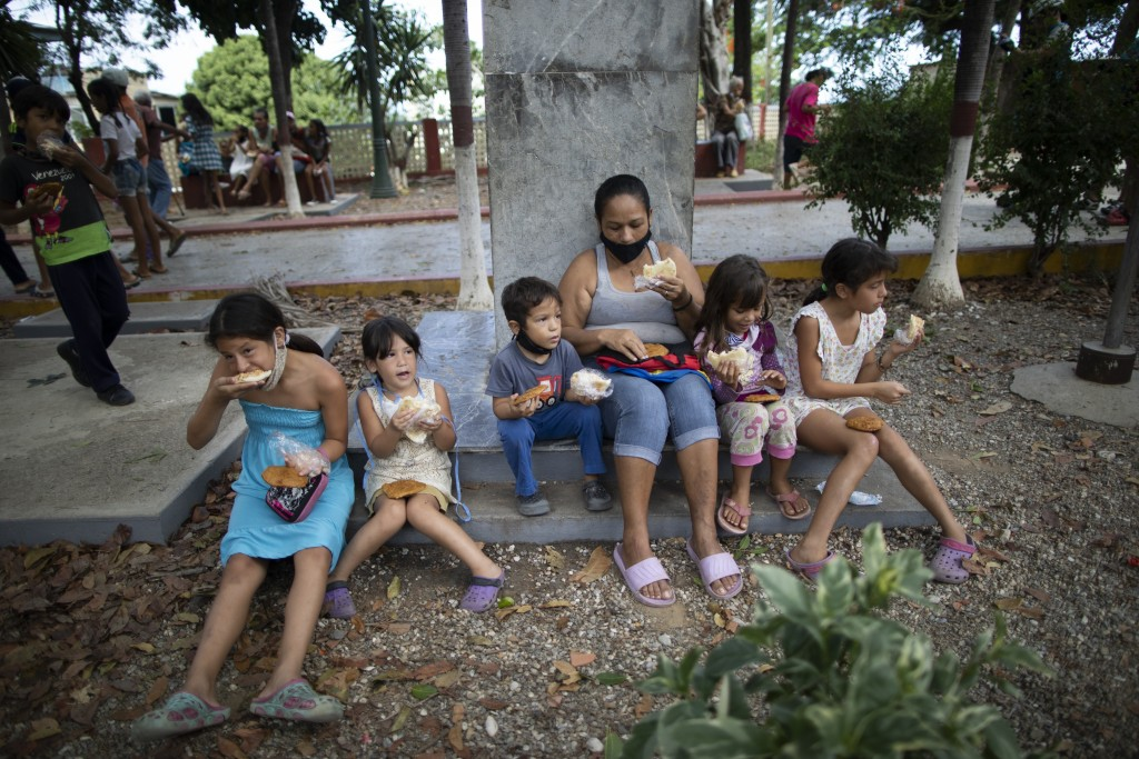 Children eat free arepas or corn flour patties, given to them by Andres Burgos, a 55-year-old publicist, in Macuto, Venezuela, Saturday Oct. 24, 2020....