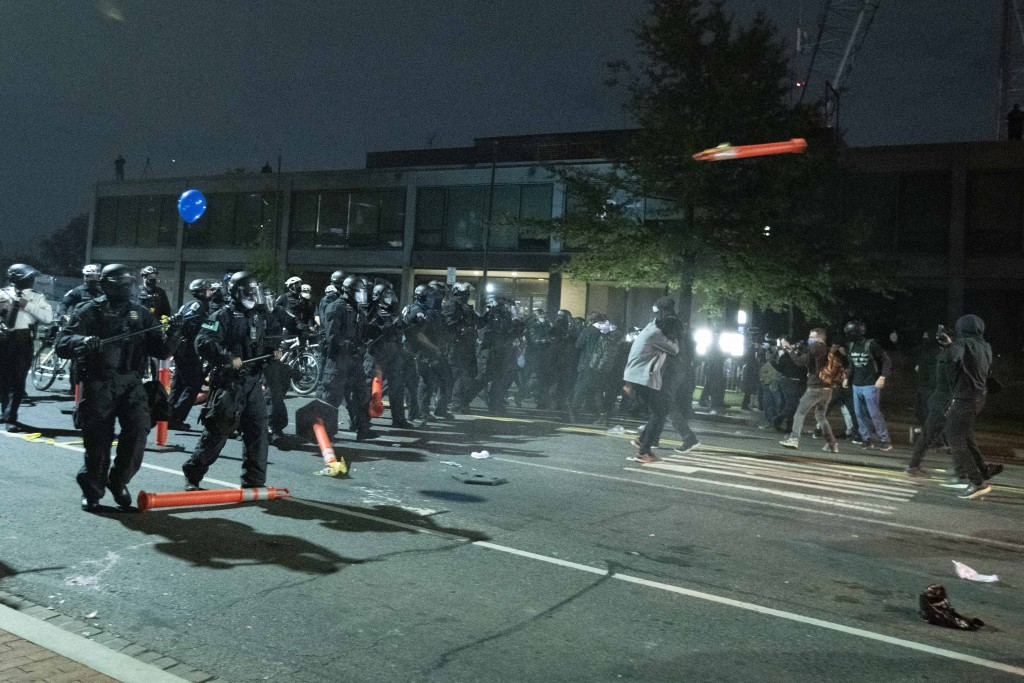 Washington Metropolitan Police Department police officers push back demonstrators outside of the fourth district police station in Washington, Wednesd...