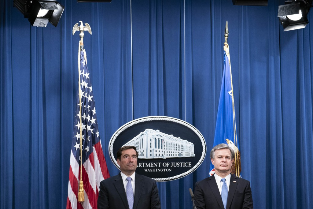 Assistant Attorney General for National Security John Demers, left, and FBI Director Christopher Wray participate in a virtual news conference at the ...