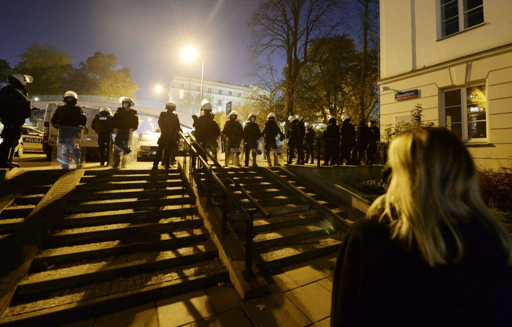 Police stand guard while protesters block the parliament in Warsaw, Poland, Wednesday Oct. 28, 2020. People across Poland stayed off their jobs and hu...
