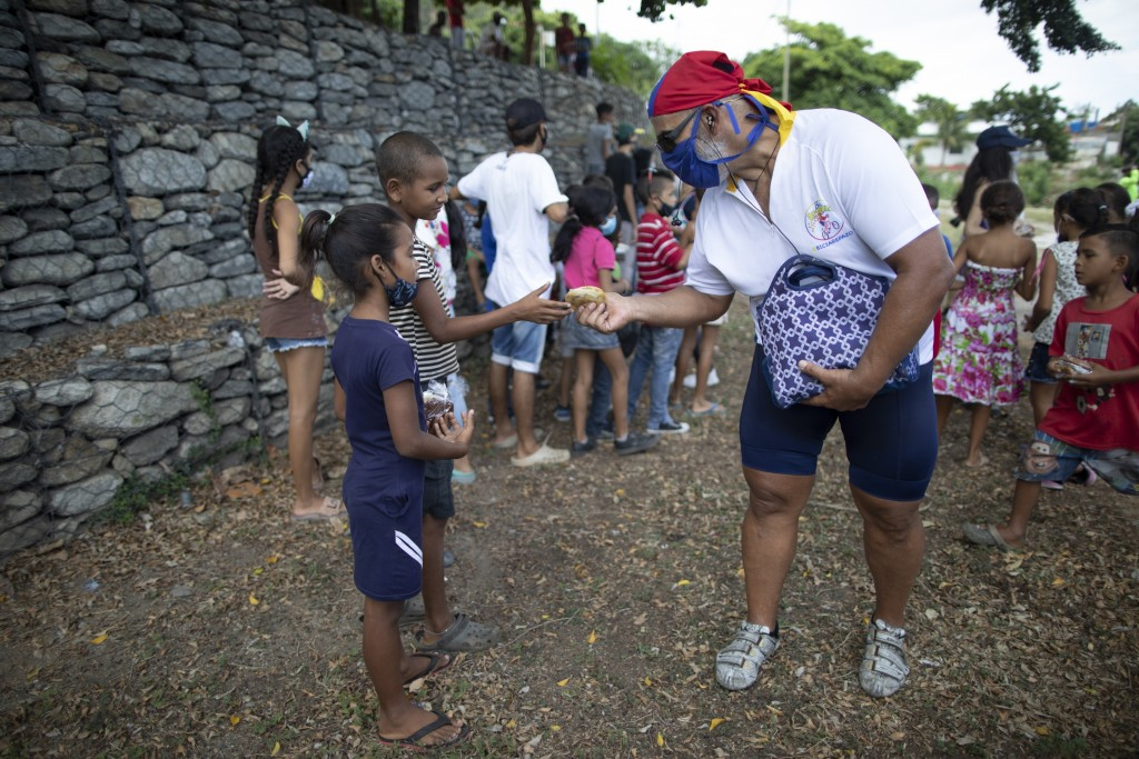 Andres Burgos, a 55-year-old publicist, hands a package of homemade arepas or corn flour patties to a child in Macuto, Venezuela, Saturday Oct. 24, 20...