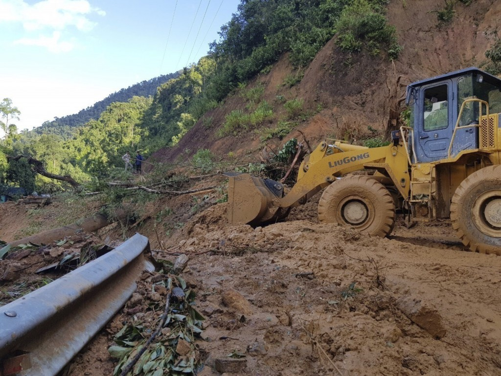 A bulldozer clears out the road damaged by landslide to access a village swamped by another landslide in Quang Nam province, Vietnam on Thursday, Oct....