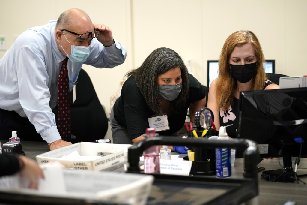 FILE- In this Oct. 26, 2020, file photo, Miami-Dade County Supervisor of Elections Christina White, right, examines signatures on vote-by-mail ballots...