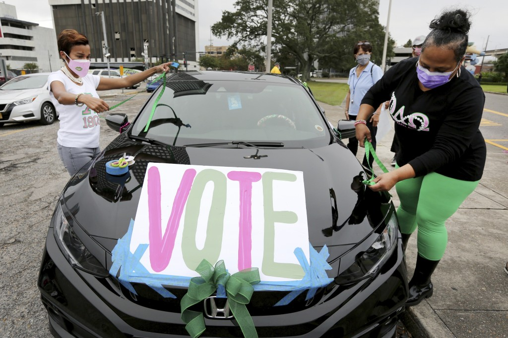 """Maurya Glaude and Angela Davis decorate a car before a """"Parade to the Polls"""" event, organized by Operation Go Vote!, a collaborative of African Americ..."""