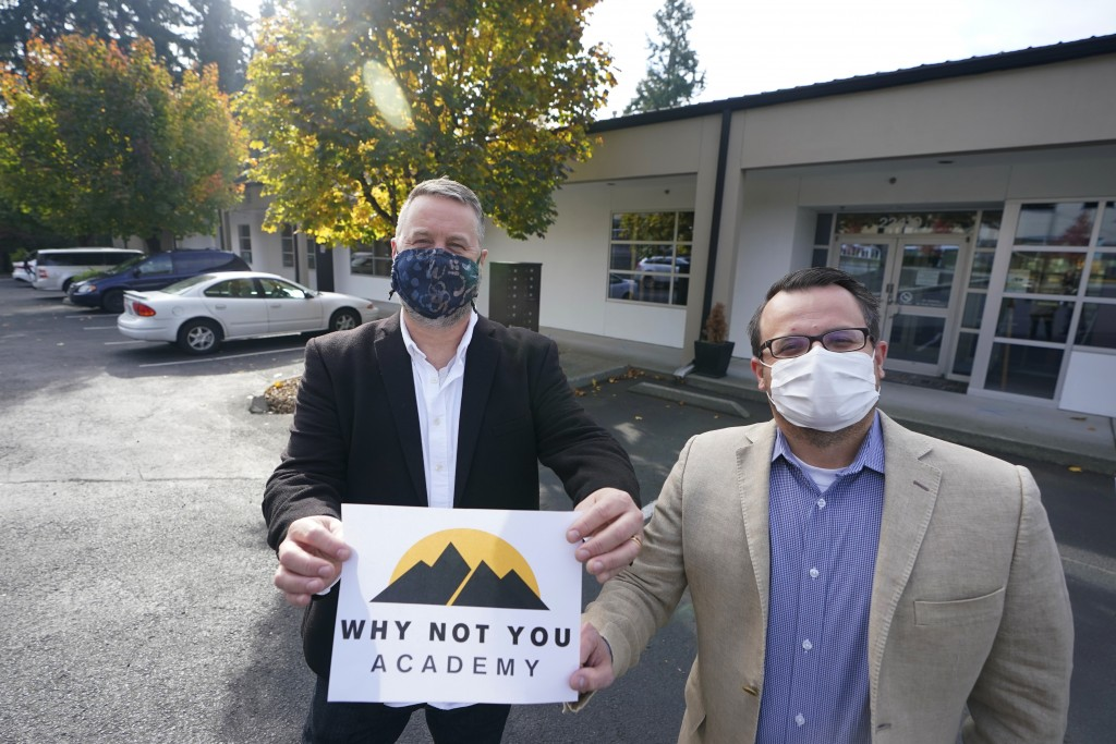 Garth Reeves, left, and Scott Canfield, co-founders of the Why Not You Academy charter school, pose for a photo with the school's new name and logo, T...