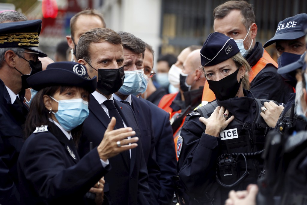 French President Emmanuel Macron, second left, and Nice mayor Christian Estrosi , third left, meet police officers after a knife attack at Notre Dame ...
