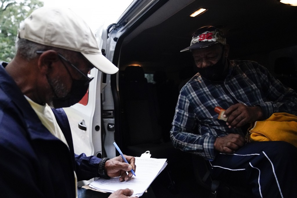 Neighborhood Assistance Corporations of America, employee, Malcom Williams, 65, of Loganville, Ga., left, works on paperwork for first time voter, Gar...