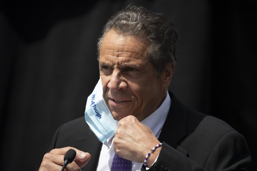 FILE - In this June 15, 2020, file photo, New York Gov. Andrew Cuomo removes a mask as he holds a news conference in Tarrytown, N.Y. The Justice Depar...