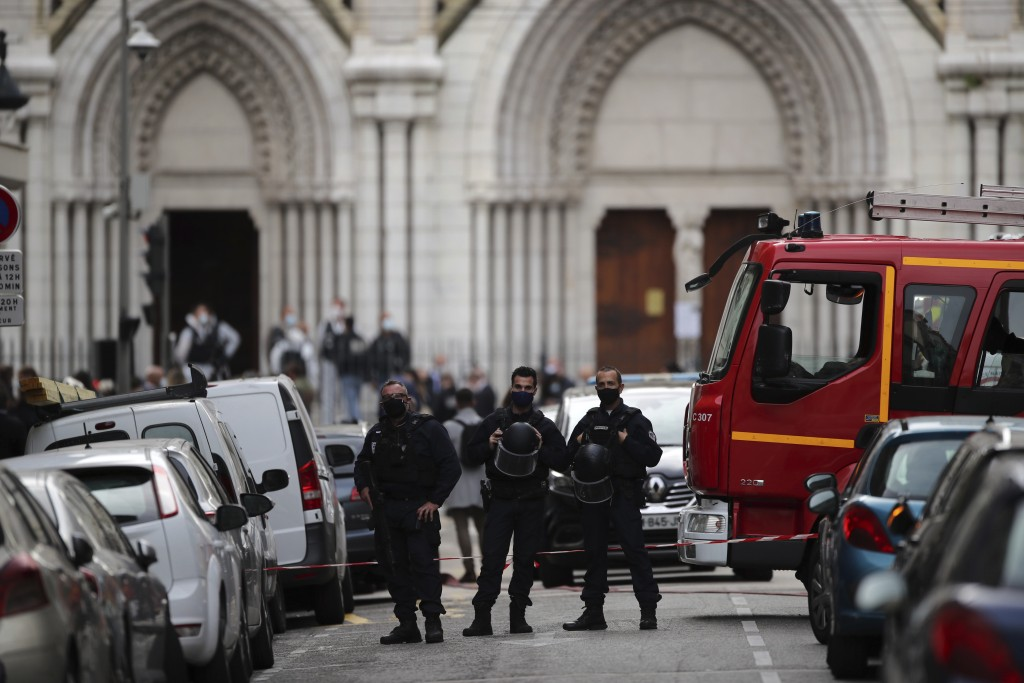 Police officers stand guard near Notre Dame church in Nice, southern France, Thursday, Oct. 29, 2020. An attacker armed with a knife killed at least t...