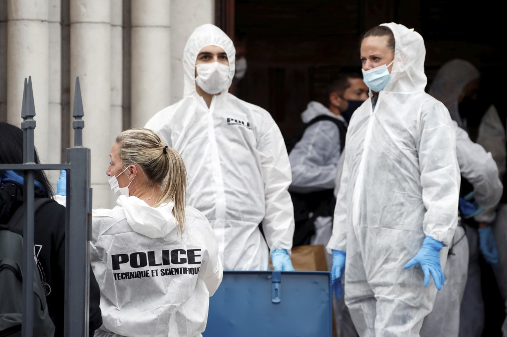 Forensic police officers inspect the scene of a knife attack at Notre Dame church in Nice, southern France, Thursday, Oct. 29, 2020. An attacker armed...