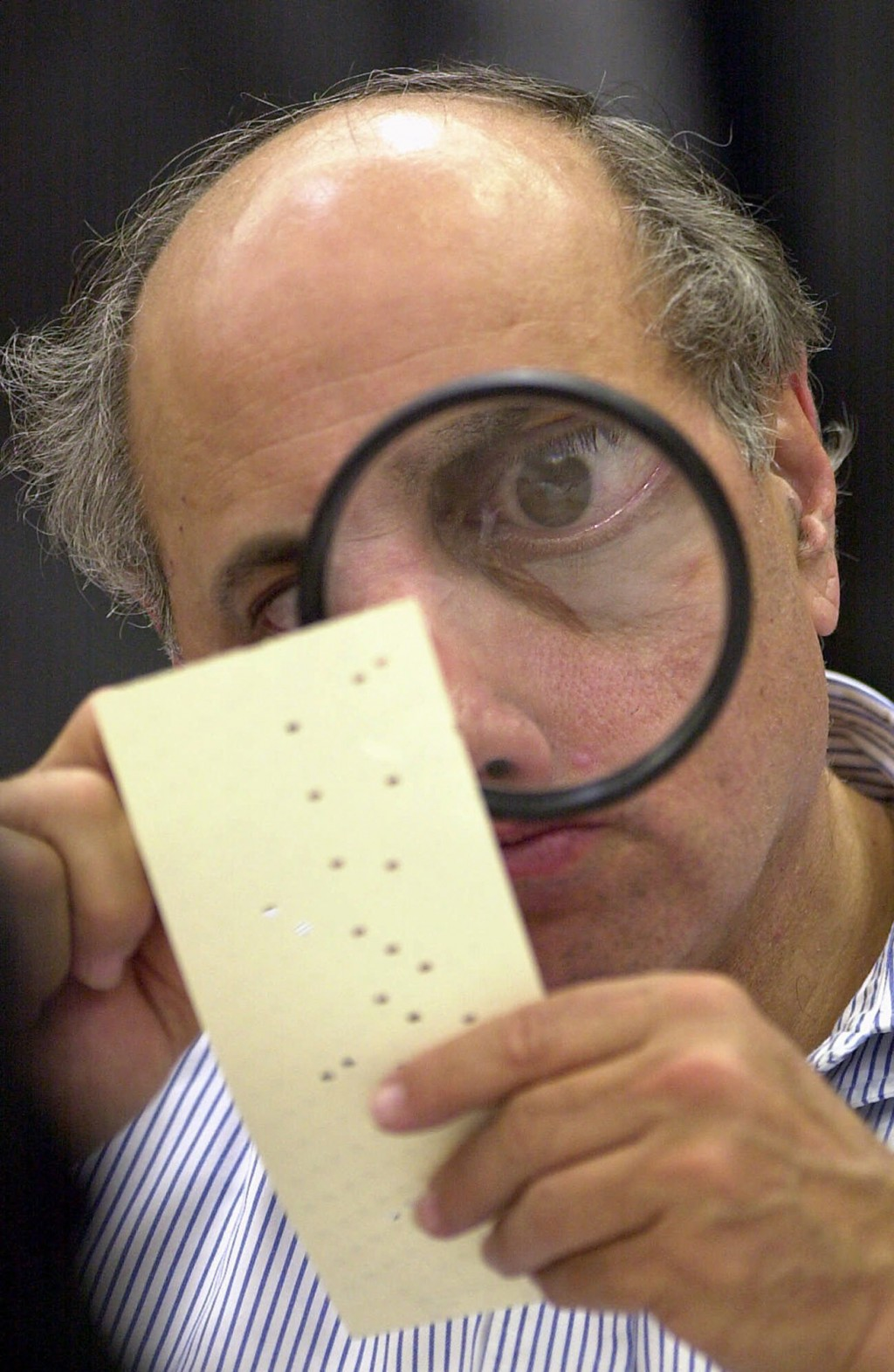 FILE - In this Nov. 24, 2000, file photo, Broward County, Fla., canvassing board member Judge Robert Rosenberg uses a magnifying glass to examine a di...