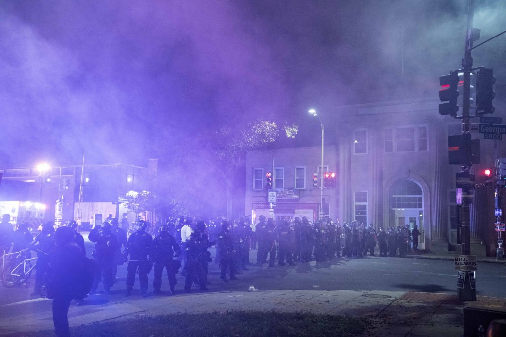 Washington Metropolitan Police Department police officers shoot smoke projectiles at demonstrators outside of the fourth district police station in Wa...