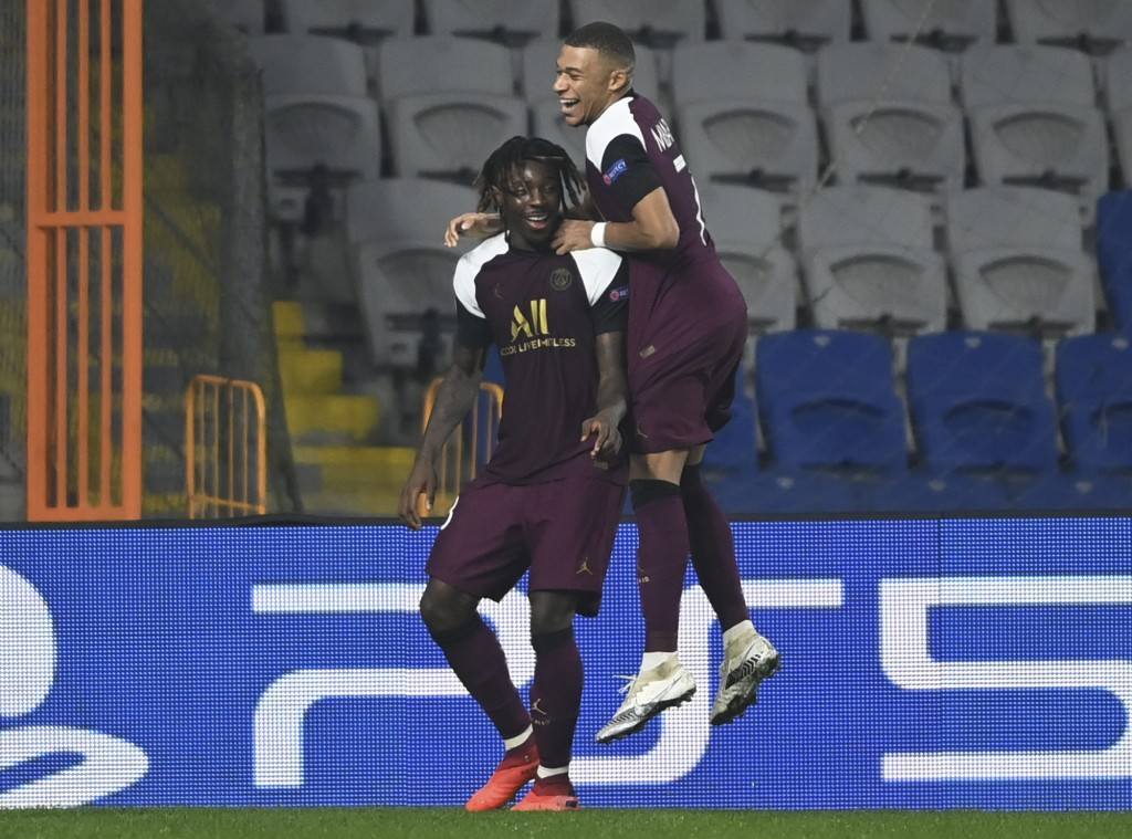 PSG's Kylian Mbappe, right, congratulates his teammate Moise Kean, left, after he scored during the Champions League group H soccer match between Basa...