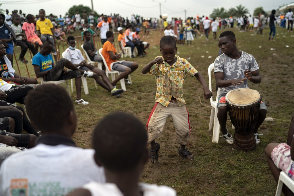 A boy dances as a supporter plays an african percussion instrument before the arrival of the Ivory Coast President Alassane Ouattara at a rally in Any...