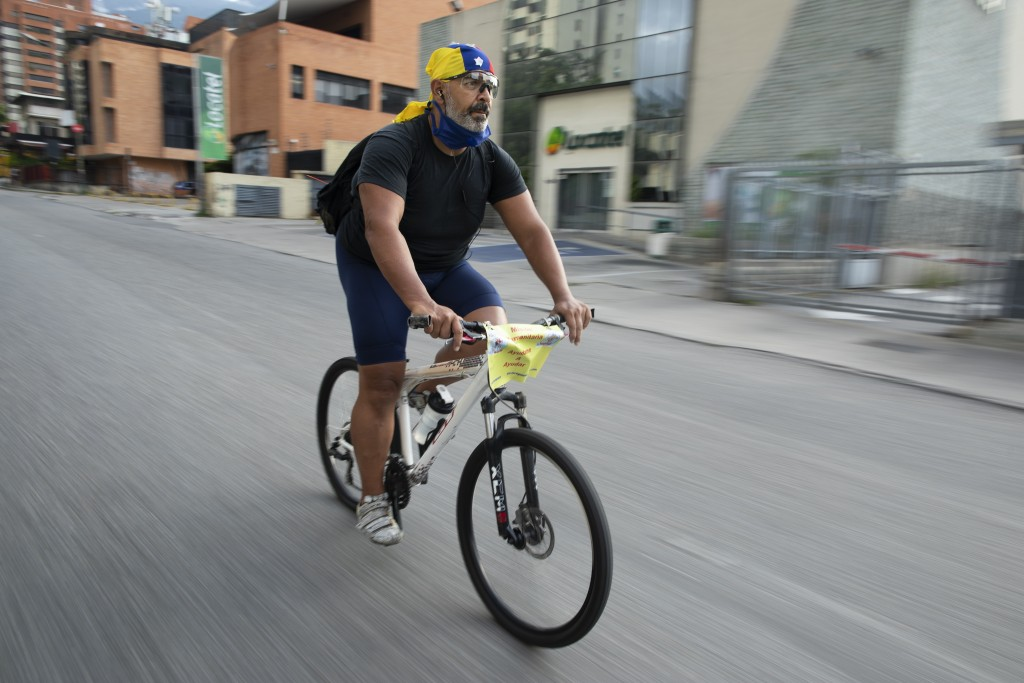 Andres Burgos, a 55-year-old publicist, rides his bicycle carrying a backpack filled with arepas or corn flour patties, in Caracas, Venezuela, Wednesd...