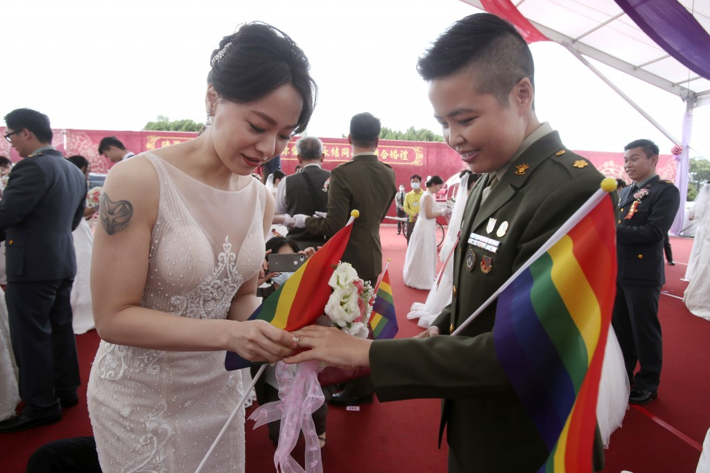 Lesbian couple Yumi Meng, left, puts a ring on Yi Wang' s finger during a military mass weddings ceremony in Taoyuan city, northern Taiwan, Friday, Oc...