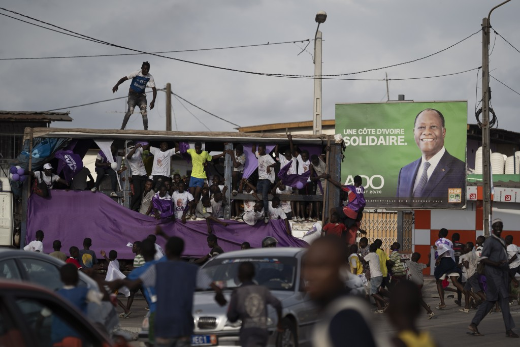 Supporters of the presidential candidate Kouadio Konan Bertin, ride a sound truck as they pass by an outdoor with a picture of the Ivory Coast Preside...