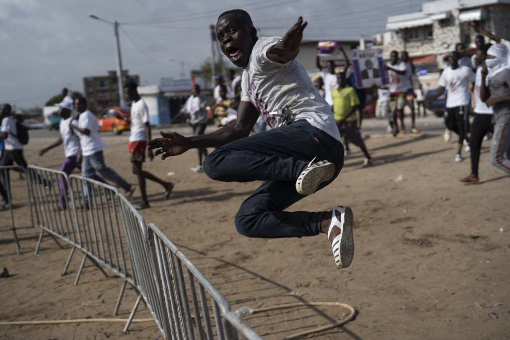A supporter of the presidential candidate Kouadio Konan Bertin, jumps a fence as he arrives at the final campaign rally in Abidjan, Ivory Coast, Thurs...
