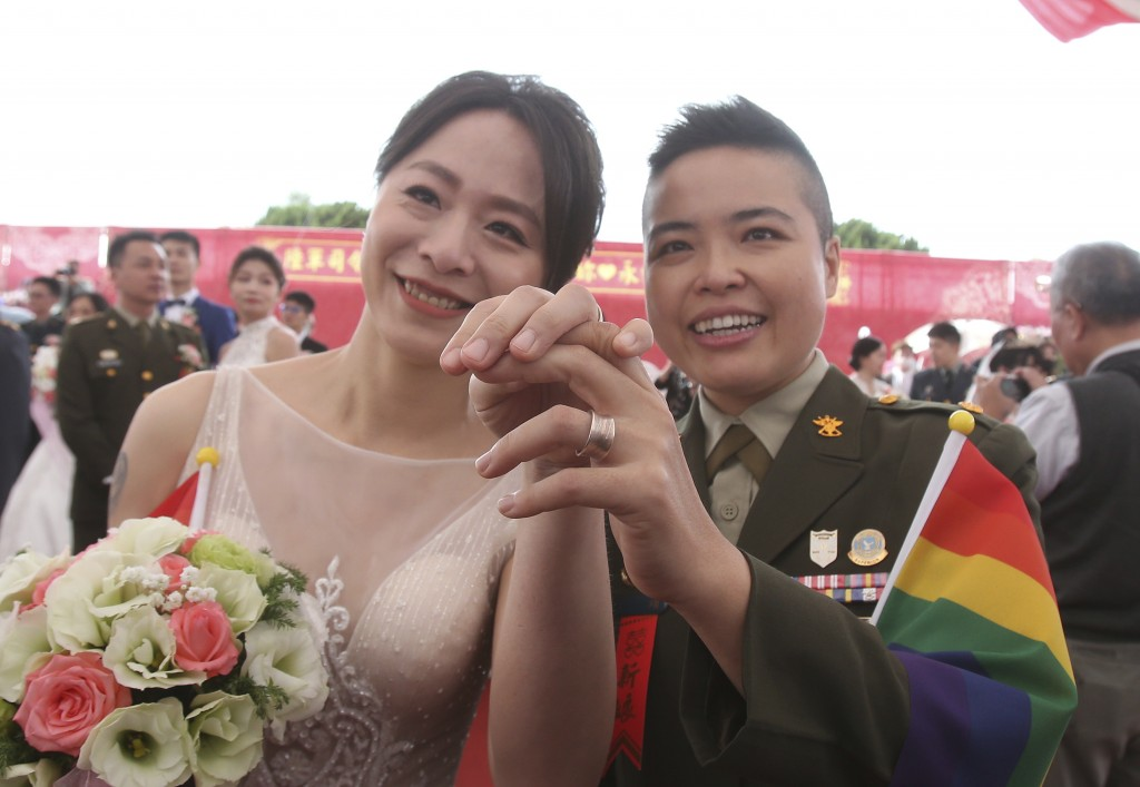 Lesbian couple Yi Wang, right, and Yumi Meng show their wedding rings during a military mass weddings ceremony in Taoyuan city, northern Taiwan, Frida...