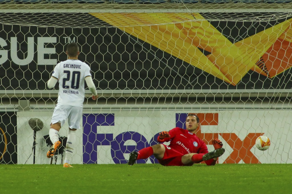 Hoffenheim's Mijat Gacinovic, left, scores past Gent's goalkeeper Davy Roef his side's third goal during the Europa League Group L soccer match betwee...