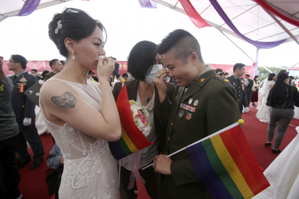Lesbian couple Yi Wang, right, and Yumi Meng reacts for joy during a military mass weddings ceremony in Taoyuan city, northern Taiwan, Friday, Oct. 30...
